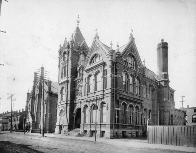 The first Hamilton Public Library, seen from the southeast from Main Street West, in a black & white photo. Centenary Methodist Church (now New Vision United Church) is seen to the west of the Victorian library building. The library is a neo-Romanesque building, with pointed roofs, round arches over the windows, and decorative brick details.