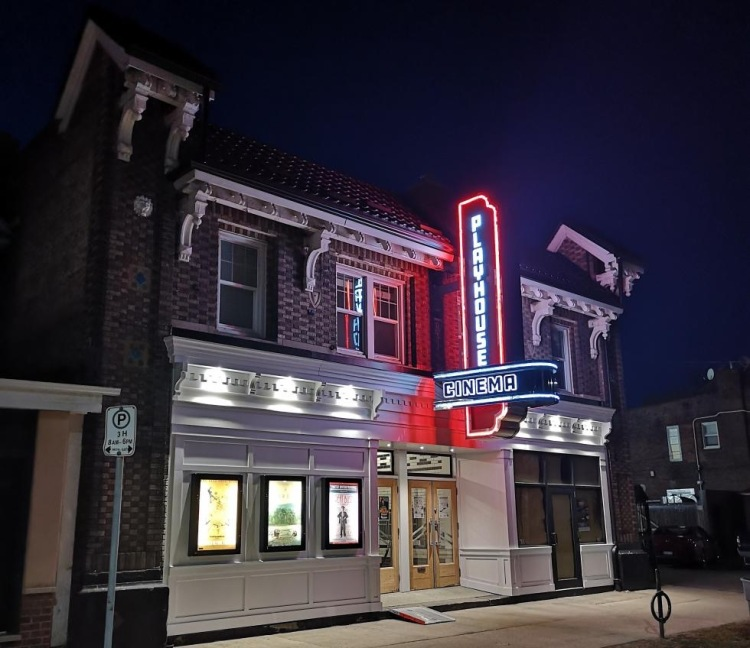 The Playhouse Cinema on Sherman Ave North, in Hamilton, Ontario, seen illuminated at night. It has a sloped roof, two-tone brickwork, white wooden trim and dentellation, white wooden panneling on the ground level, and a blue & red neon sign.