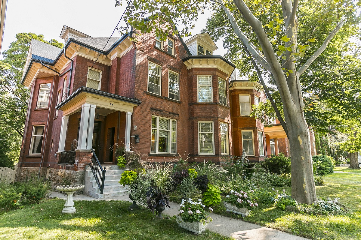 The westernmost of two grand, late-Victorian semis in red brick with cream trim and a tall old tree in the front, in Durand, Hamilton. Seen on a sunny day, with sunlight dappling the lush front garden.