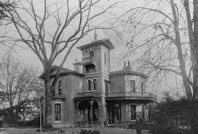 Smiley's Castle, or Rose Arden, a buff-brick mansion with large trees and a man standing in front